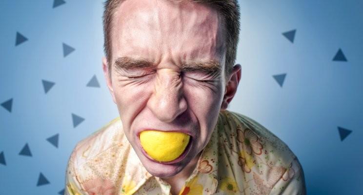 Man sucking on lemon